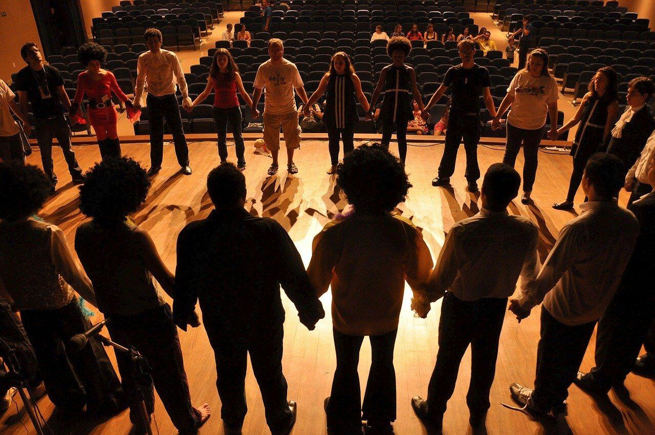 Des acteurs forment un cercle sur une scène de spectacle