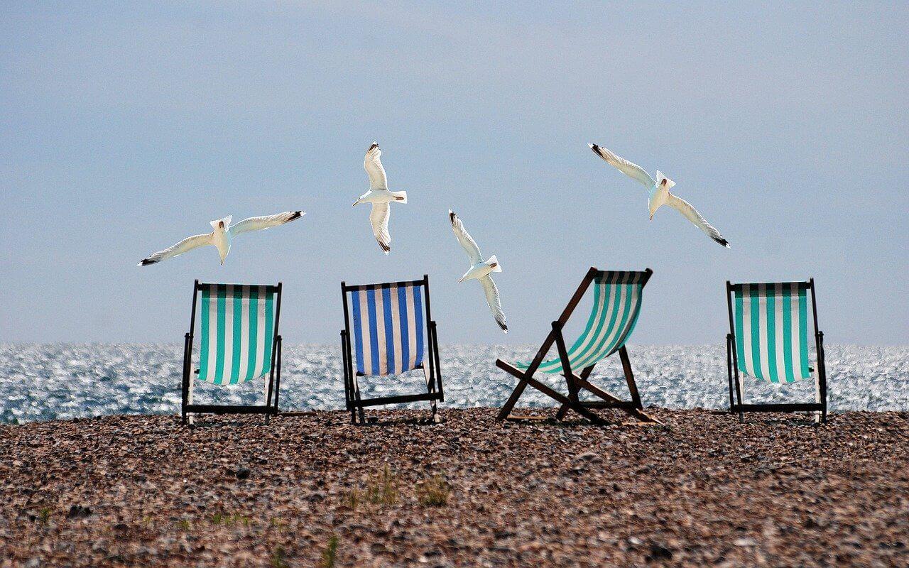 4 chaises longues sur une plage déserte.
